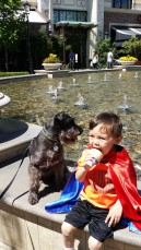 Ice cream, a fountain and a beautiful day! He loves his superman cape